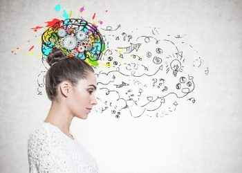 Side view of a calm and beautiful young european woman with a bun wearing a white sweater. A concrete wall with a cog brain and a business strategy sketch